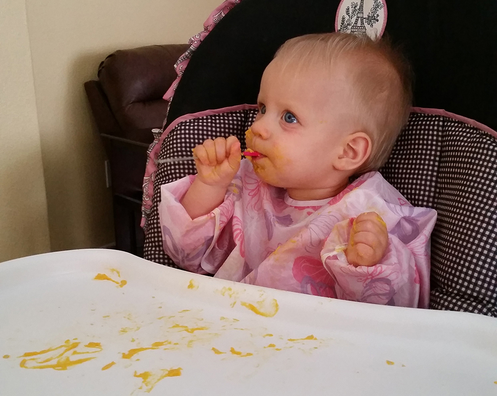 Messy baby eating from the spoon